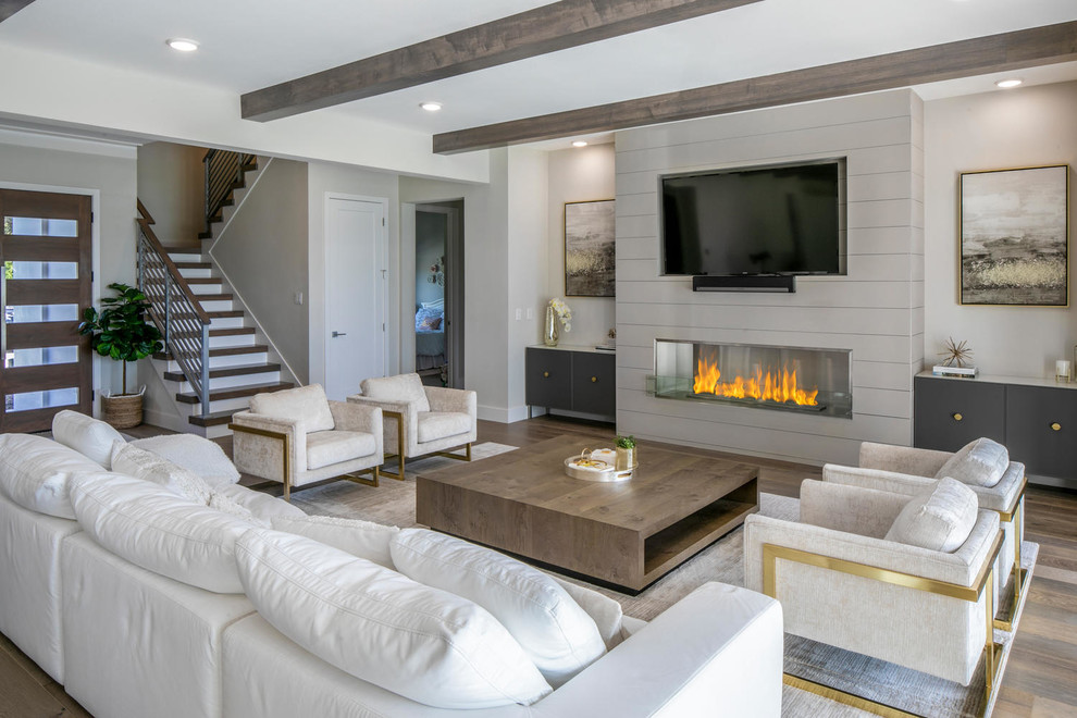 Example of a huge minimalist open concept medium tone wood floor and brown floor living room design in Tampa with white walls, a wood fireplace surround, a wall-mounted tv and a ribbon fireplace
