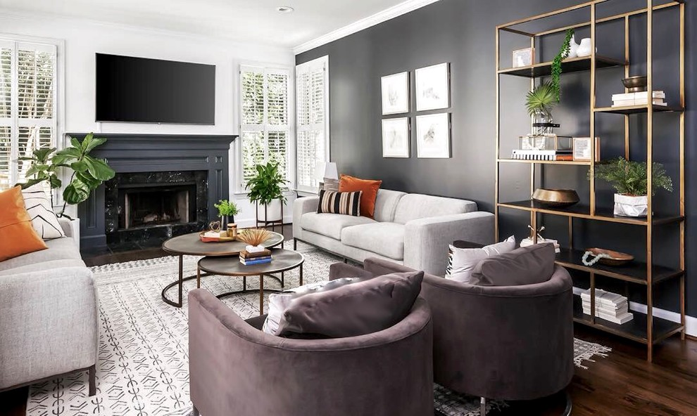 Inspiration for a mid-sized scandinavian open concept dark wood floor and brown floor living room remodel in Atlanta with a standard fireplace, a wood fireplace surround, a wall-mounted tv and black walls
