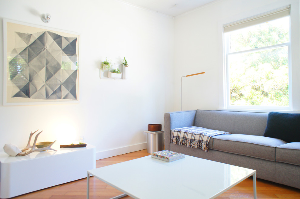 Example of a small minimalist open concept medium tone wood floor living room design in Seattle with white walls, no fireplace and no tv