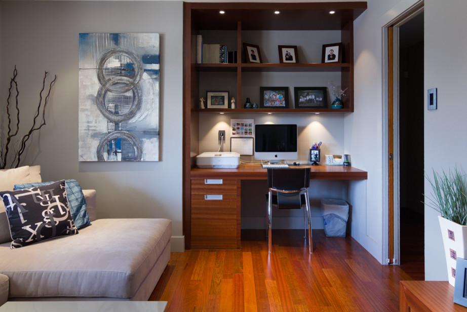 Small minimalist medium tone wood floor living room library photo in Ottawa with white walls