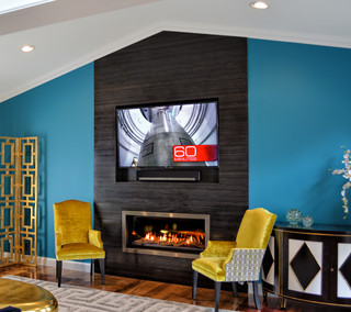 This modern renovation creates a focal point for a cool and modern living room with a linear fireplace surrounded by a wall of wood grain granite.  The TV nook