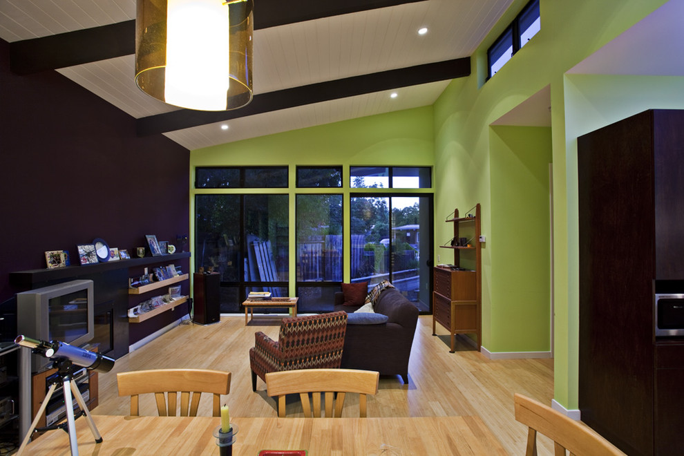 Inspiration for a mid-sized modern open concept light wood floor and beige floor living room remodel in San Francisco with green walls, a ribbon fireplace, a metal fireplace and a media wall