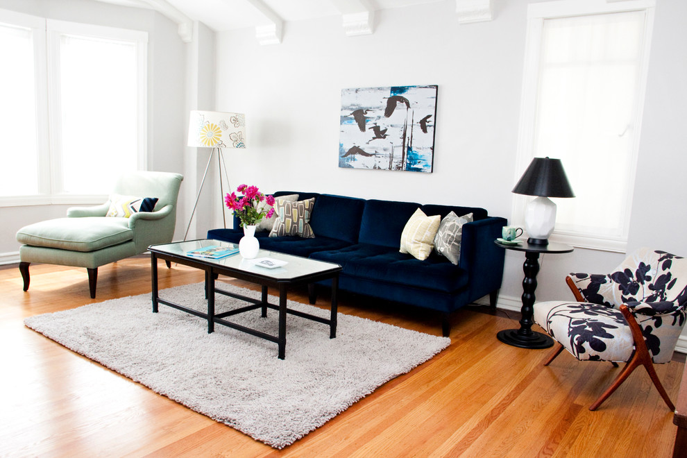 Living room - mid-sized eclectic enclosed and formal medium tone wood floor living room idea in Los Angeles with white walls and no tv