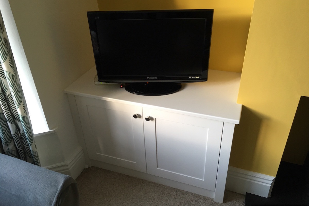 Modern White Shaker Base Cabinet Against Yellow Walls