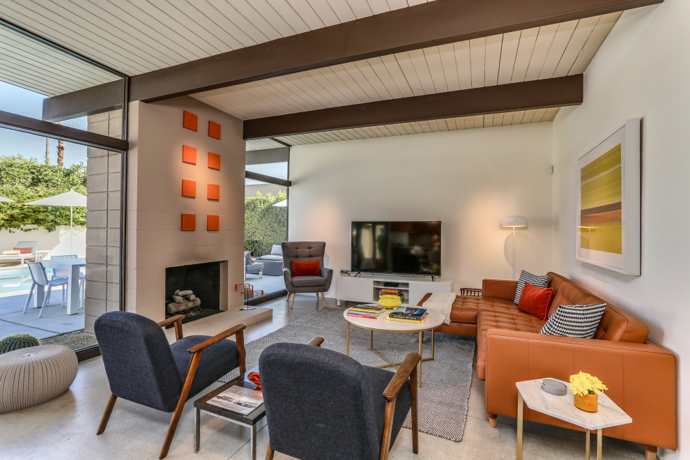 Inspiration for a 1960s open concept concrete floor, beige floor, exposed beam and shiplap ceiling living room remodel in Other with white walls, a standard fireplace and a tv stand