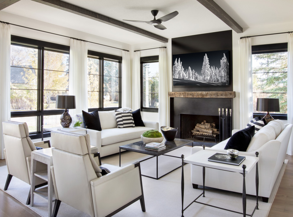 Inspiration for an expansive country formal living room in Austin with white walls, a standard fireplace, a freestanding tv and brown floor.