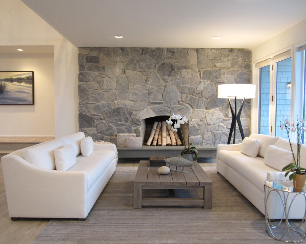 Example of a mid-sized beach style formal and open concept light wood floor living room design in New York with beige walls, a standard fireplace and a stone fireplace