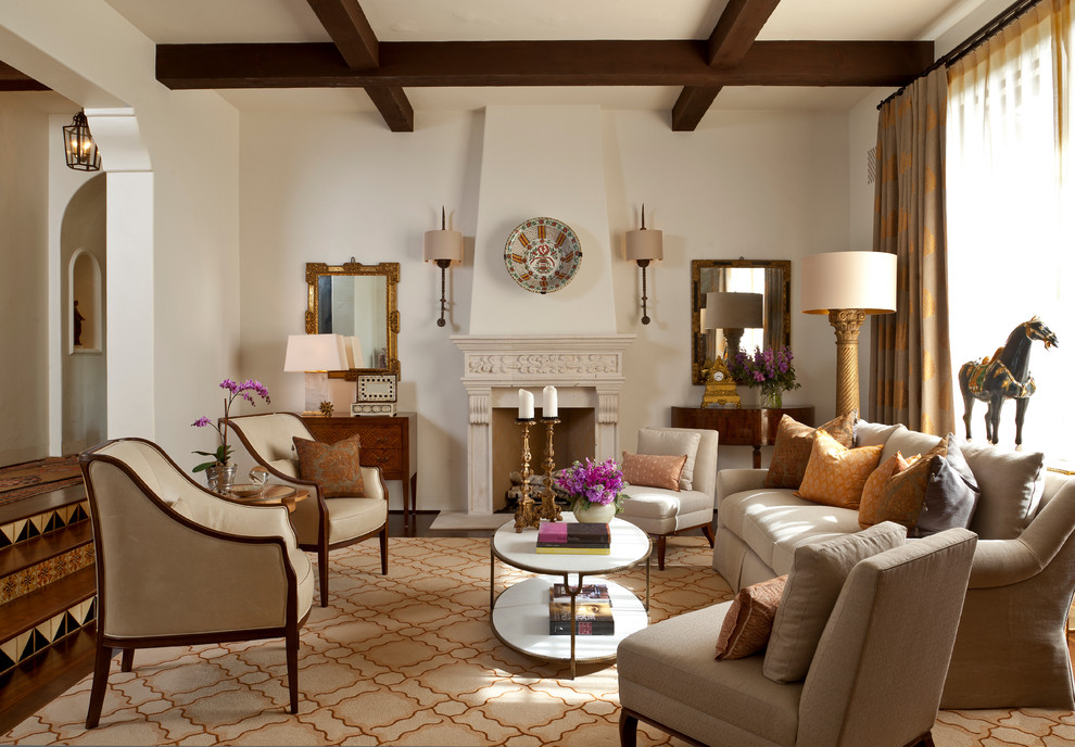 Inspiration for a large mediterranean enclosed and formal dark wood floor and brown floor living room remodel in Santa Barbara with beige walls, a standard fireplace, no tv and a plaster fireplace