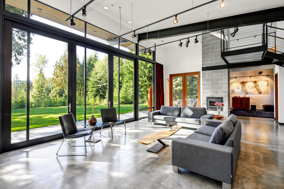 Urban open concept concrete floor and gray floor living room photo in Seattle with white walls and a standard fireplace