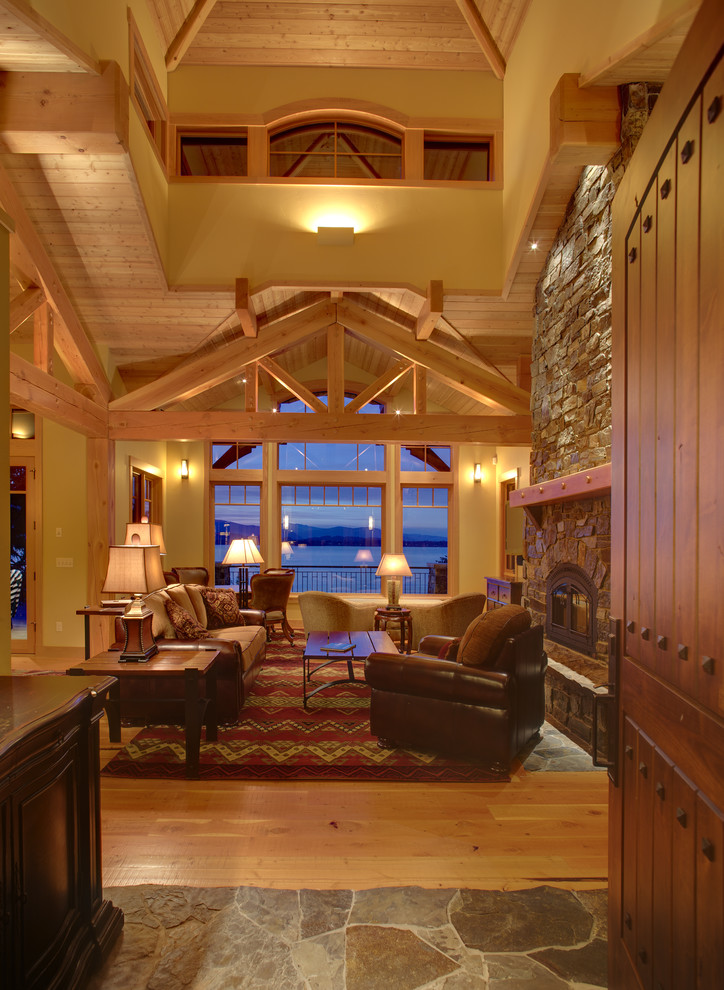 Inspiration for a mid-sized rustic loft-style and formal light wood floor and beige floor living room remodel in Boise with yellow walls, a standard fireplace, a stone fireplace and no tv
