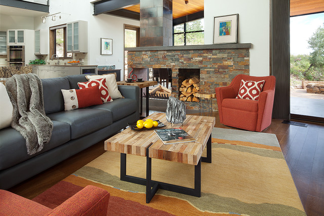 Large trendy open concept medium tone wood floor living room photo in Albuquerque with gray walls, a two-sided fireplace, a stone fireplace and a wall-mounted tv