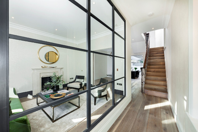 Inspiration for a large timeless medium tone wood floor living room remodel in London with white walls