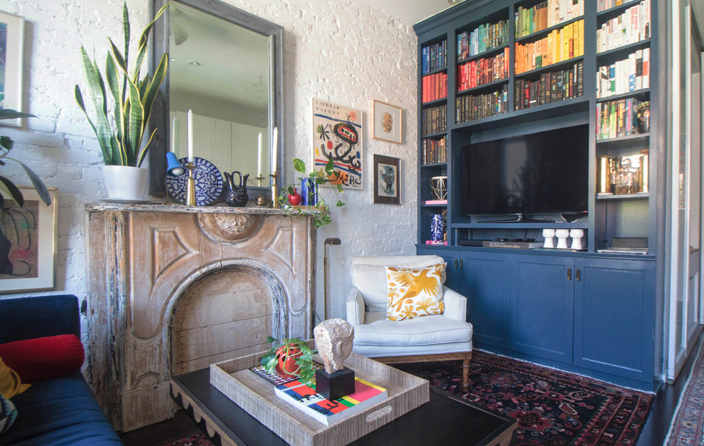 Living room library - eclectic dark wood floor living room library idea in New York with white walls and a media wall