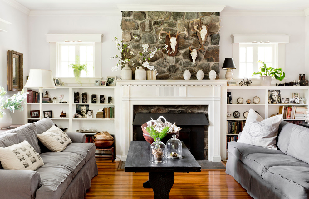 Example of a classic medium tone wood floor living room design in New York with white walls, a standard fireplace and a stone fireplace