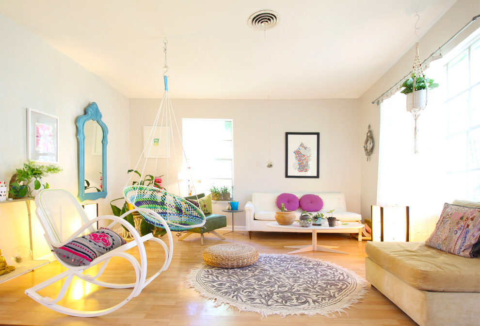 Example of an eclectic light wood floor living room design with white walls and no fireplace