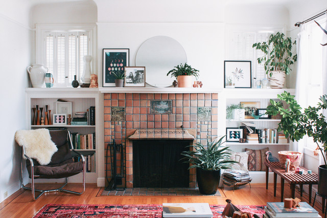 Inspiration for a small bohemian living room in San Francisco with a standard fireplace, a tiled fireplace surround, white walls, medium hardwood flooring and no tv.