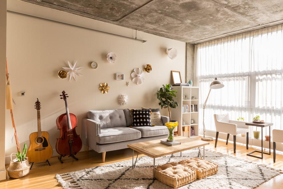 Living room - industrial medium tone wood floor and brown floor living room idea in San Francisco with beige walls