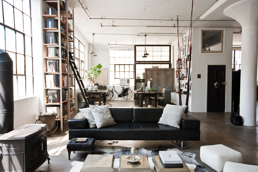 Example of an urban concrete floor and gray floor living room design in New York with a wood stove