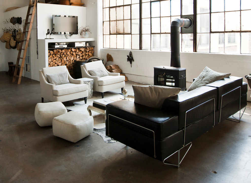 Example of an urban open concept concrete floor living room design in New York with a wood stove
