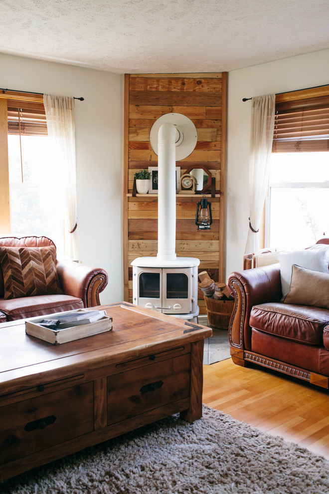 Inspiration for a mid-sized farmhouse enclosed medium tone wood floor living room remodel in Seattle with white walls, a wood stove, a wood fireplace surround and a tv stand