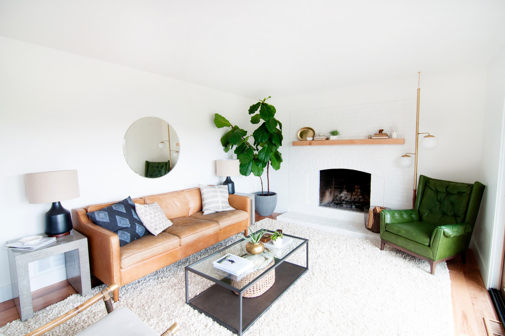 Example of a mid-sized 1950s open concept light wood floor living room design in Denver with white walls, a standard fireplace, a brick fireplace and no tv
