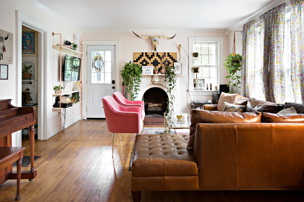 Example of an eclectic enclosed medium tone wood floor and brown floor living room design in Nashville with pink walls, a standard fireplace, a plaster fireplace and a wall-mounted tv