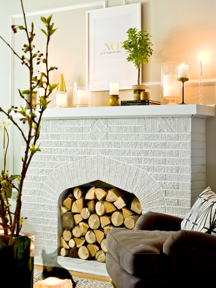 Example of an eclectic living room design in Chicago with beige walls, a standard fireplace and a brick fireplace