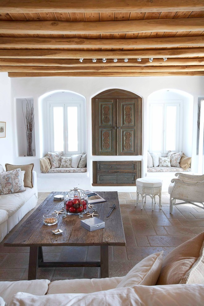 Living room - mediterranean living room idea in Other with white walls and a concealed tv
