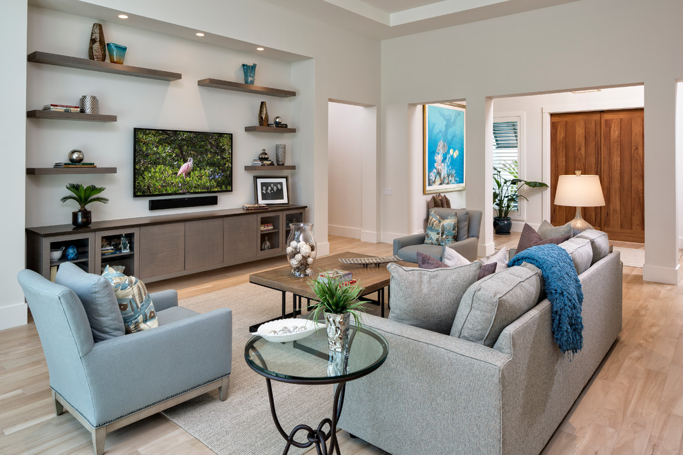 Large beach style open concept light wood floor living room photo in Miami with white walls and a wall-mounted tv