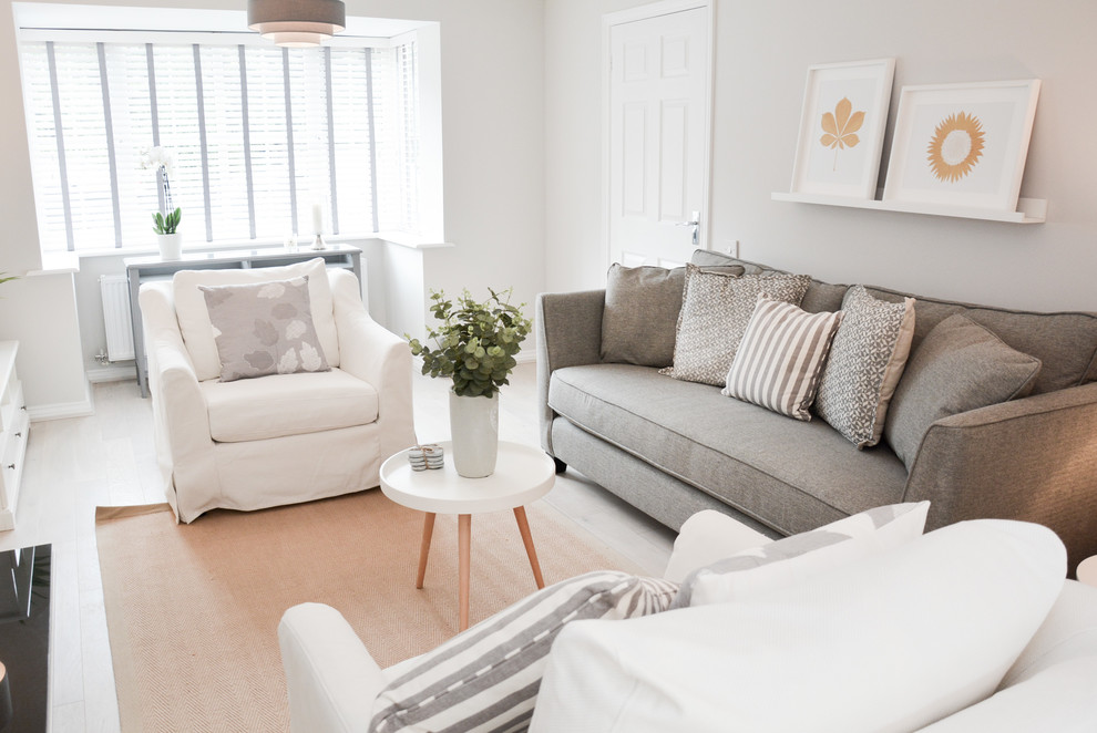 Inspiration for a scandinavian light wood floor and beige floor living room remodel in Hampshire with white walls and a tv stand