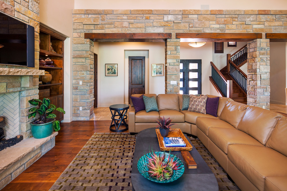 Transitional medium tone wood floor living room photo in Austin with beige walls, a standard fireplace and a stone fireplace