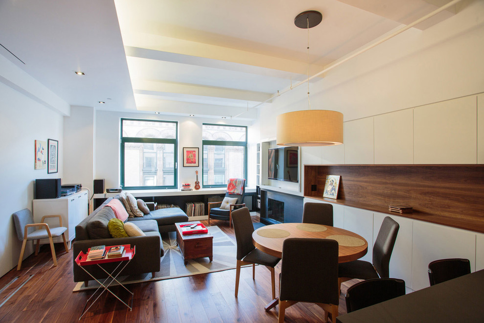 Example of a small trendy open concept medium tone wood floor and brown floor living room design in New York with a standard fireplace, a wall-mounted tv, a metal fireplace and white walls