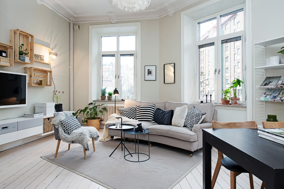 Example of a large danish formal painted wood floor living room design in Gothenburg with a wall-mounted tv and beige walls