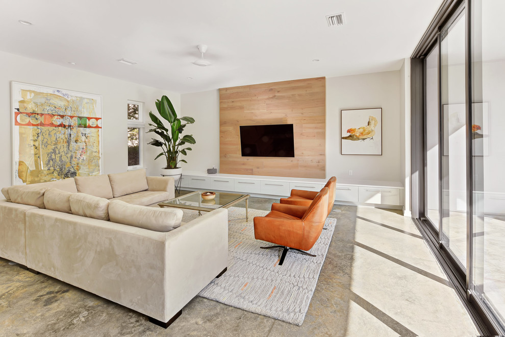 Example of a large minimalist enclosed gray floor and concrete floor living room design in Jacksonville with white walls, a wall-mounted tv and no fireplace