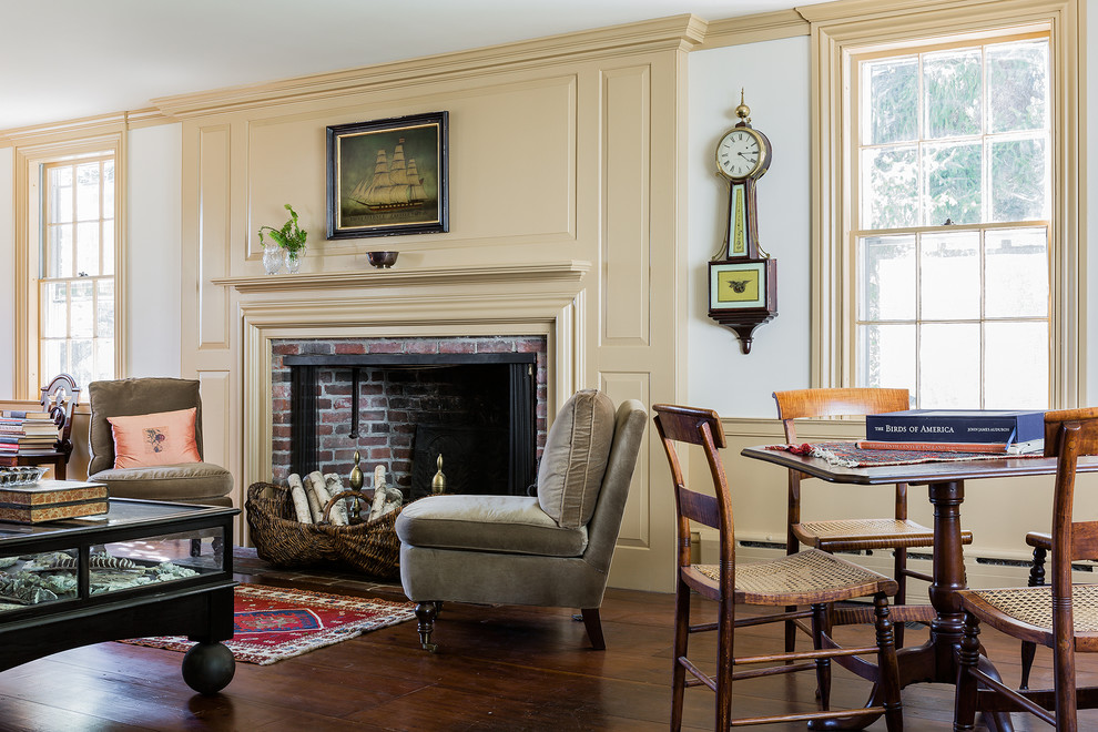 Example of a classic enclosed living room design in Boston with yellow walls, a standard fireplace, a brick fireplace and no tv