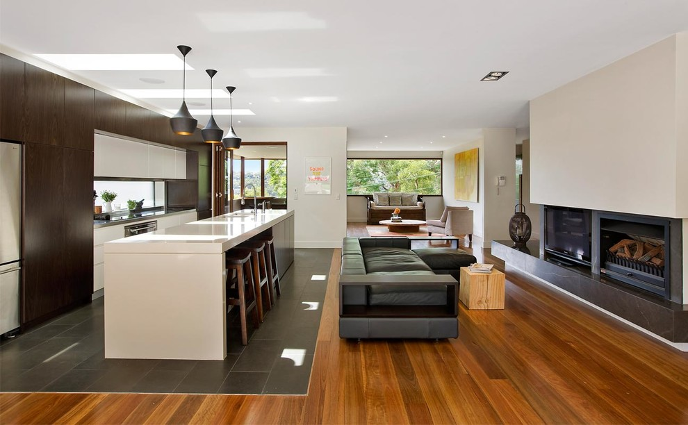 Trendy formal and open concept medium tone wood floor living room photo in Sydney with beige walls, a ribbon fireplace and a media wall