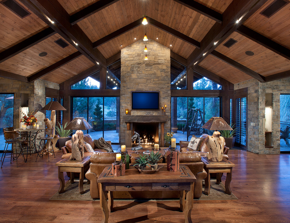 Inspiration for a mid-sized rustic open concept medium tone wood floor living room remodel in Phoenix with a standard fireplace, a stone fireplace and a wall-mounted tv