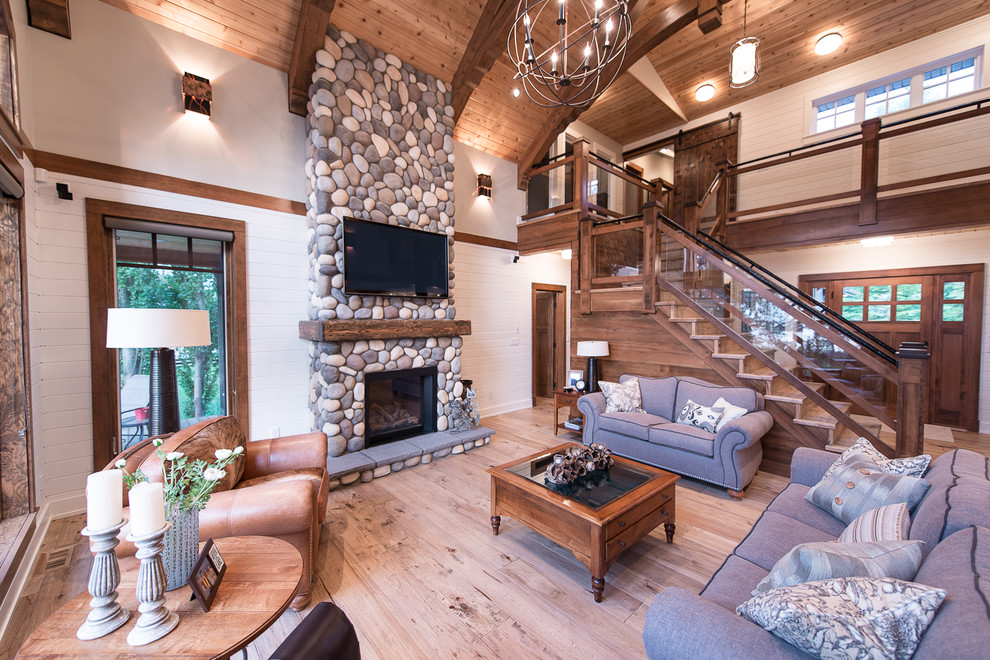 Living room - traditional living room idea in Vancouver with a standard fireplace, a stone fireplace and a wall-mounted tv