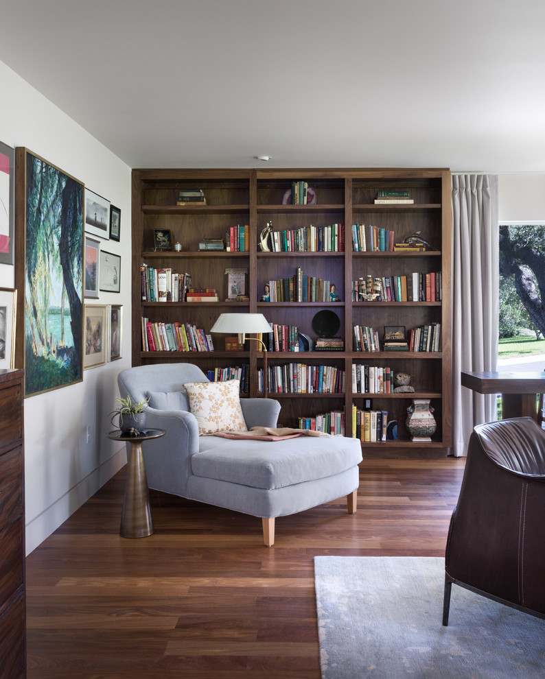 Example of a large trendy dark wood floor living room library design in Austin with white walls, a standard fireplace and a brick fireplace