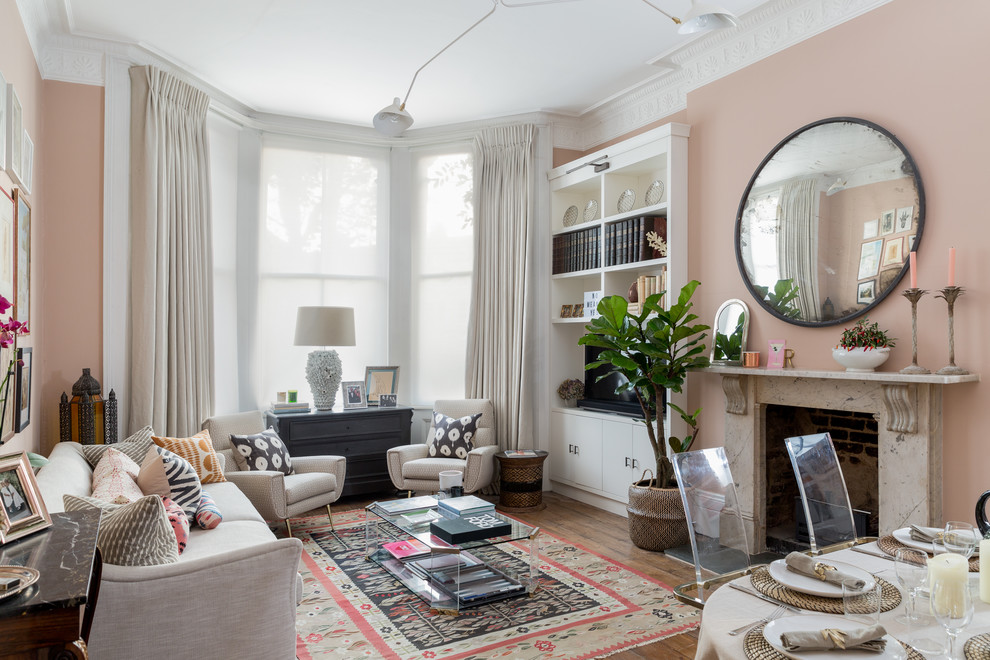 Transitional open concept medium tone wood floor and brown floor living room photo in London with pink walls, a standard fireplace and a media wall