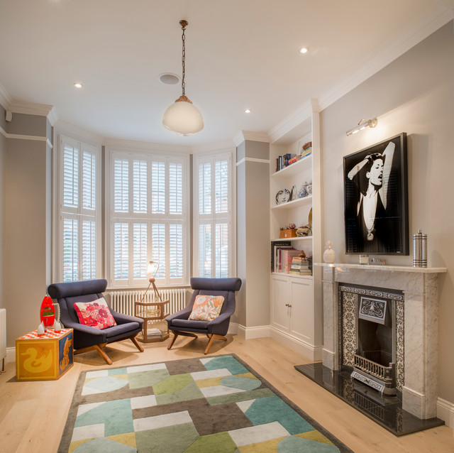 Design ideas for a traditional living room in London with grey walls, light hardwood flooring and a standard fireplace.
