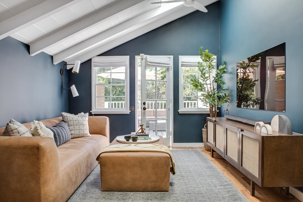 Living room - scandinavian enclosed medium tone wood floor and brown floor living room idea in Orange County with blue walls and a wall-mounted tv