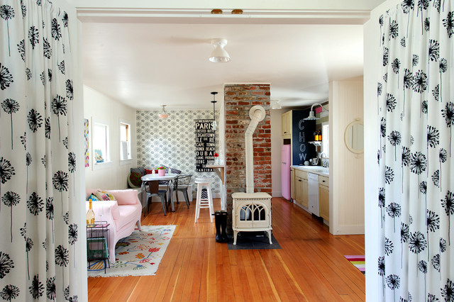 Inspiration for an eclectic open concept medium tone wood floor living room remodel in Other with a wood stove