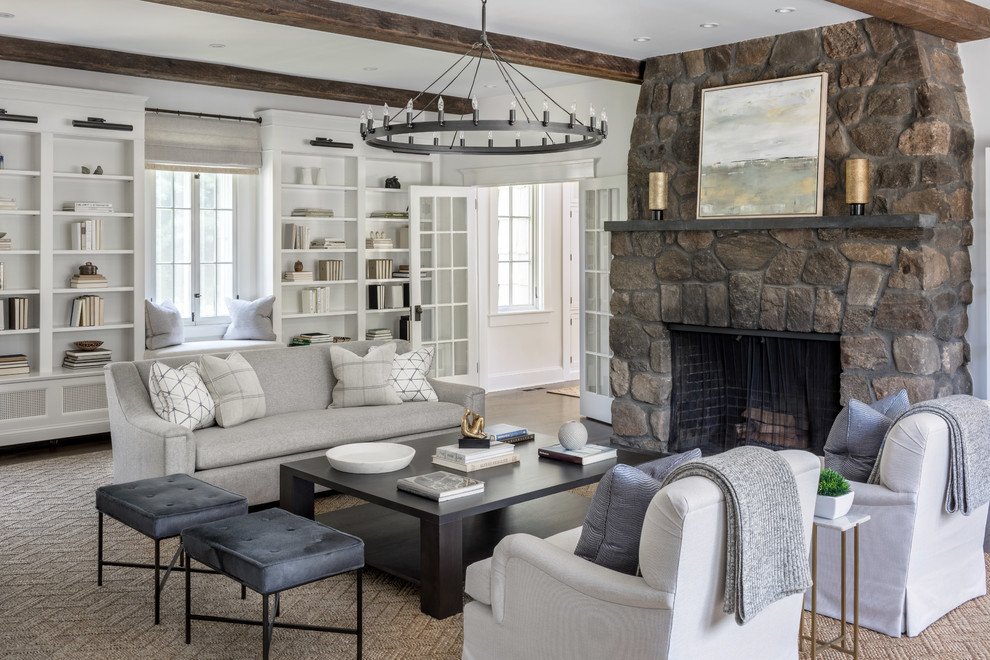 Example of a transitional dark wood floor and brown floor living room design in New York with white walls, a standard fireplace and a stone fireplace