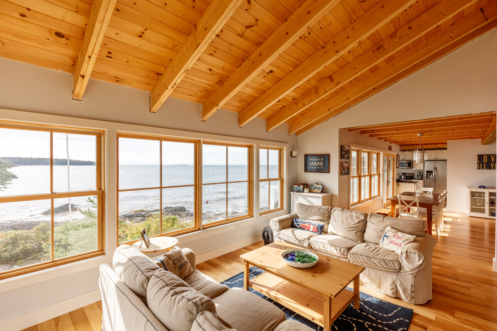 Example of a mid-sized beach style open concept light wood floor living room design in Portland Maine with white walls, no fireplace and no tv
