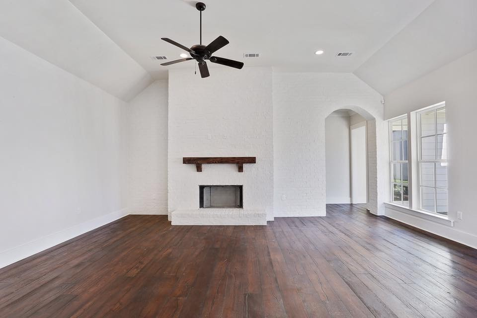 Mid-sized elegant open concept dark wood floor and brown floor living room photo in New Orleans with gray walls, a standard fireplace, a brick fireplace and no tv
