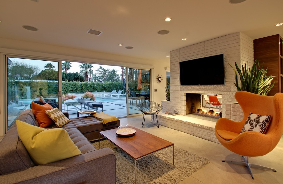 Living room - mid-sized contemporary open concept concrete floor living room idea in Los Angeles with white walls, a two-sided fireplace, a brick fireplace and a wall-mounted tv