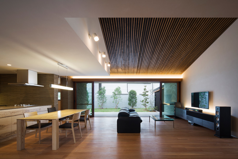 Living room - contemporary open concept medium tone wood floor and beige floor living room idea in Kobe with white walls and a wall-mounted tv