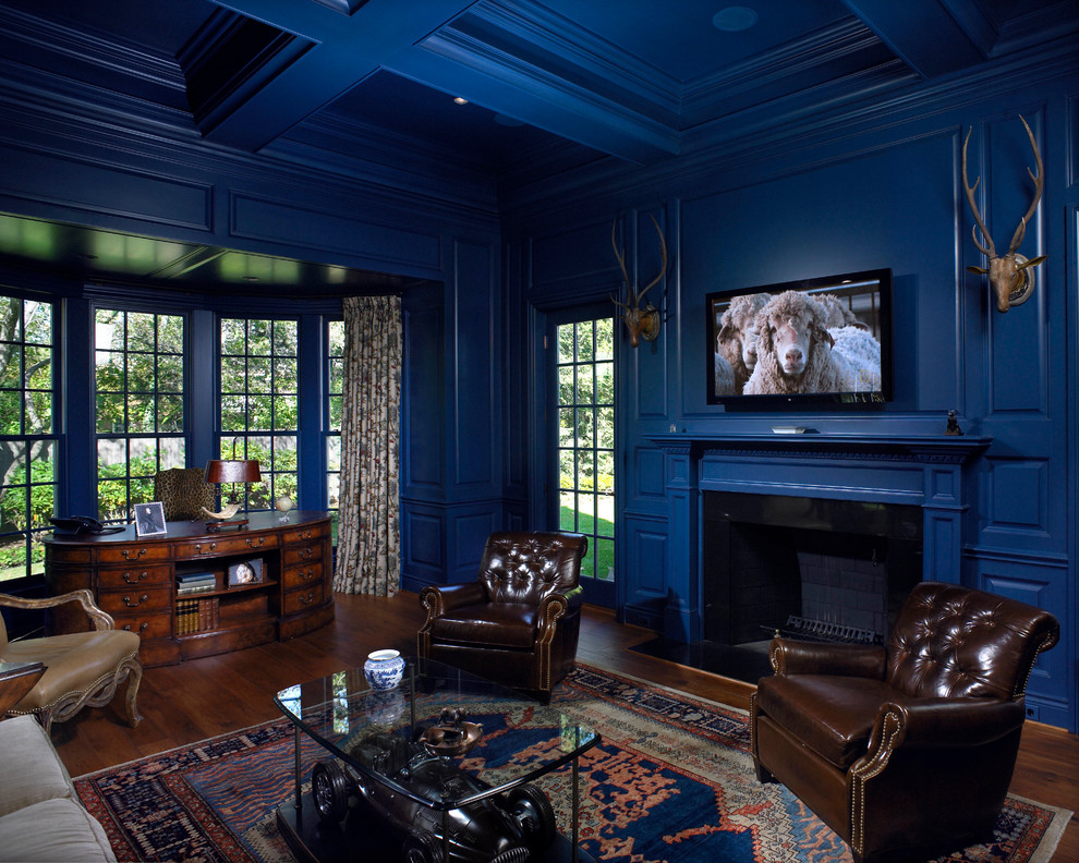 Elegant living room photo in Detroit with blue walls, a standard fireplace, a wood fireplace surround and a wall-mounted tv