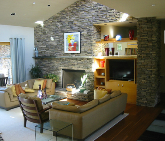 Mid-sized loft-style medium tone wood floor living room photo in Portland with beige walls and a stone fireplace